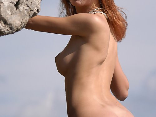 Busty redhead naked by the sea