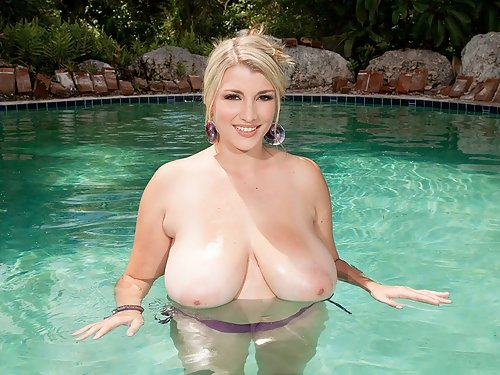 Chubby blonde soaks up her huge tits in the pool