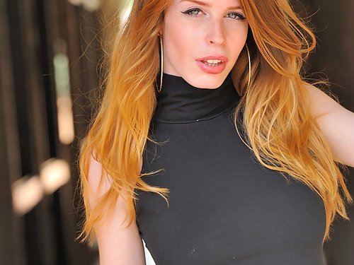 Natural redhead toying by a building