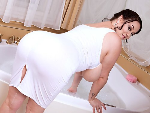Chubby busty brunette soaps up her massive boobs