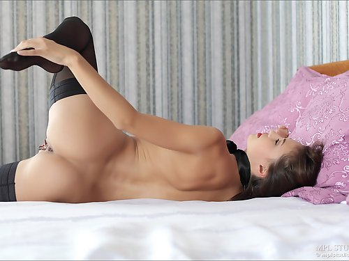 Shaved brunette in stockings in bed