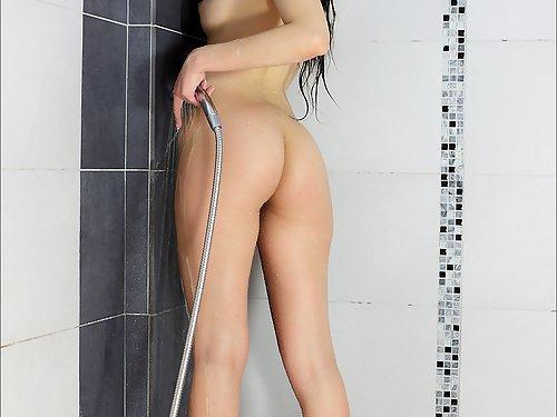 Shaved brunette fingering in the bathtub