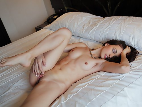 Black-haired hottie with small nipples masturbating in bed