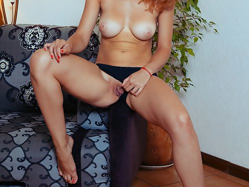 Busty redhead with tan lines spreads her shaved pussy