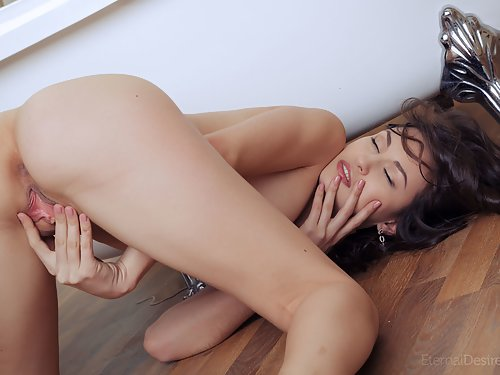 Black-haired hottie with small nipples rubs her shaved pussy
