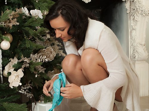 Busty black-haired hottie Sanita shows off her bush for Christmas