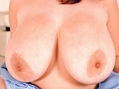 Sexy redhead with huge boobs stripping