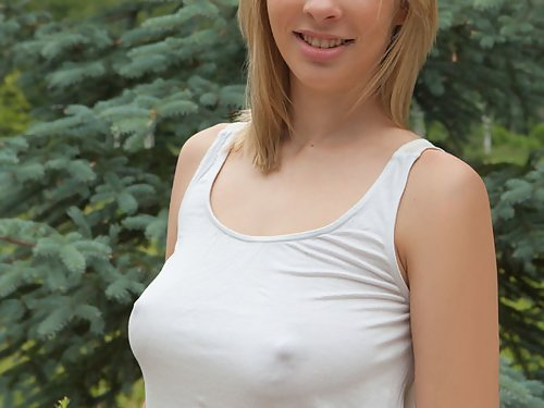 Freckled blonde with big tits nude by a tree