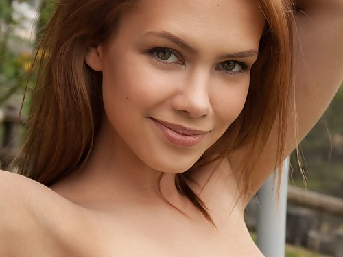 Shaved redhead babe nude in the backyard