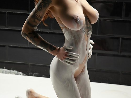 Tattooed babe with big tits playing with paint