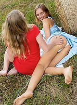 Lesbians licking and fingering each other in a field