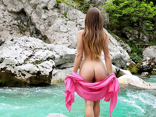 Lovely girl exposes her huge pussy lips by a river