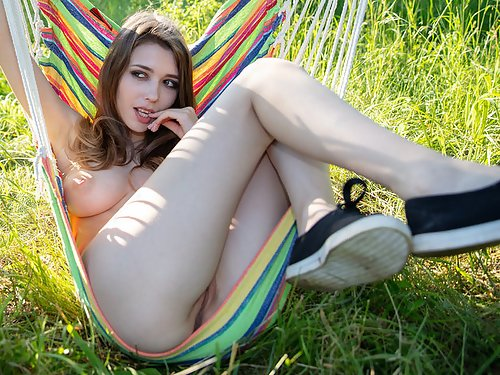 Busty brunette spreads her ass by a hammock