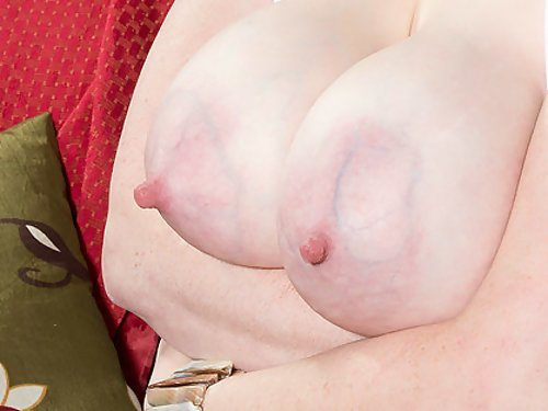 Chubby redhead plays with her big lactating tits