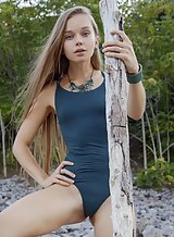 Long-haired blonde teen shows off her hairy bush outdoors