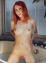 Redhead fingering her shaved pussy in the bathtub
