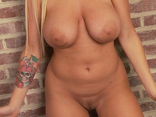 Shaved blonde shows off her big tits