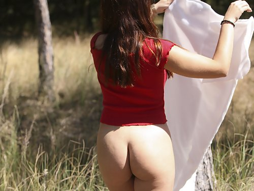 Chubby brunette with puffy nipples stripping by a tree