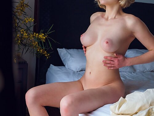 Blue-eyed blonde with pale skin plays with her bald pussy in bed